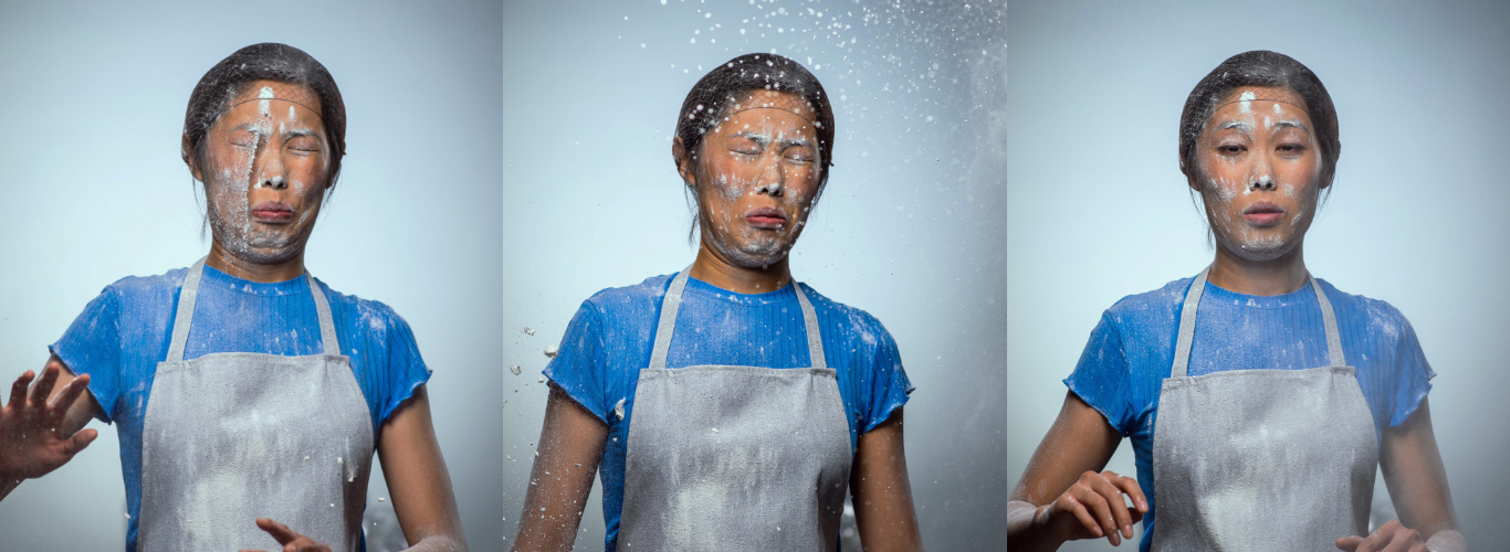 A series of three images of a woman wearing a blue shirt, white apron and hair net having flour exploding in her face.